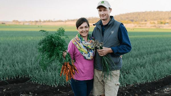 Gen and Ed Windley standing with a bunch of carrots in front of their carrot crop