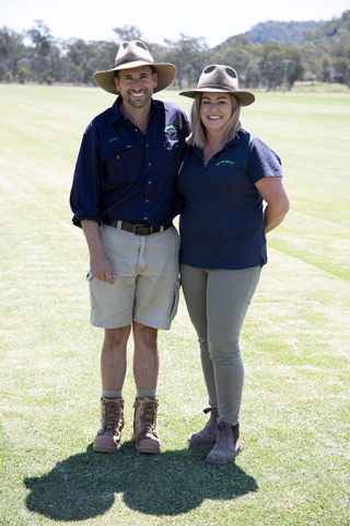A man and a woman wearing matching shirts and hats stand in a turf crop.