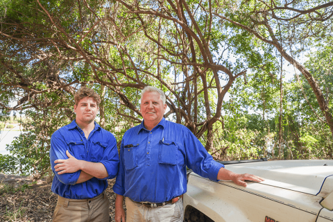 A father and son farming duo inspect a water source leaning against a farm ute.