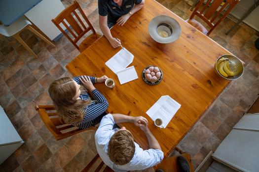 Three people sitting around kitchen table