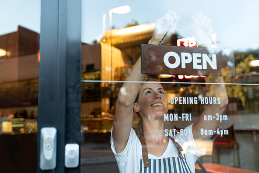 Woman putting up 'open' sign  on shop front