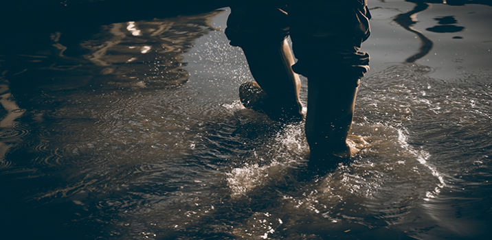 A man wearing gum boots and trousers walks through shallow flood water