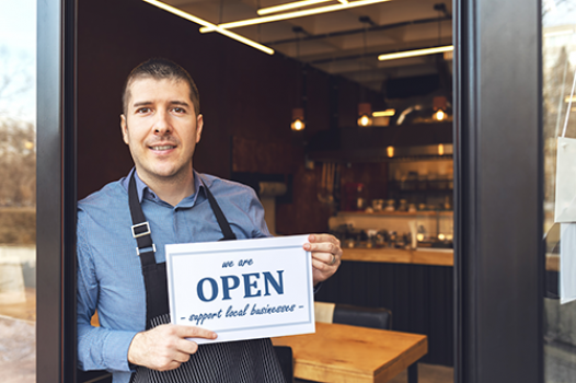 Man standing at a shop front with 'We are open sign'