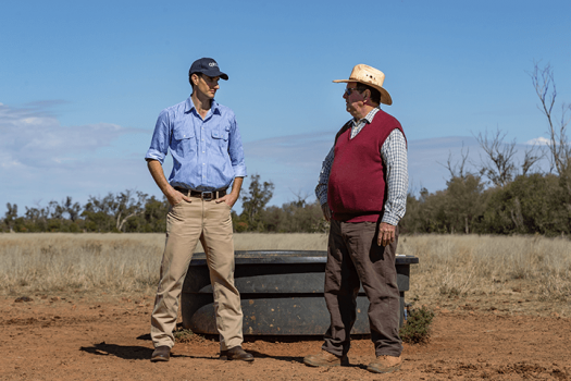 Two men chat in a cattle paddock beside a water trough.